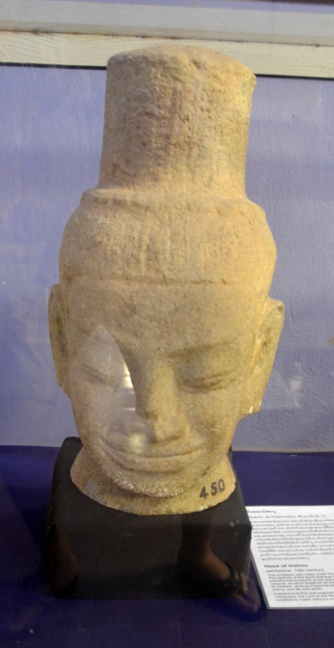 Head of Vishnu: Sandstone, 12th century: This sculpture was made under the influence of Angkor's Bayon style. The serenity of the facial features is typical of art of this period. The peaceful benevolence of the deities the Angkorian style depicts is unusual, as other Buddhist art traditions tend to represent all aspects of creation, striking a balance between good and evil, wrath and mercy, and life and death. It seems that this was originally a sculpture of the Buddhist deity Lokesvara, the Lord of the World, but his elaborate hairstyle has been modified to make Vishnu's crown.